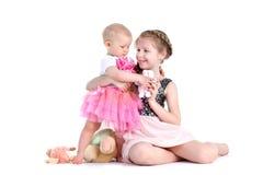 hermanas 8 años y bebés de 11 meses en blanco Fotografía de archivo