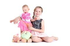 Hermanas 8 años y bebés de 11 meses en blanco Imagenes de archivo