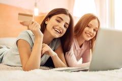 Hermanas adolescentes alegres que presentan con una tarjeta de crédito de oro Imagen de archivo libre de regalías