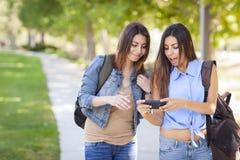 Hermanas adultas gemelas de la raza mixta que comparten experiencia del teléfono celular Fotos de archivo libres de regalías