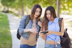 Hermanas adultas jovenes del gemelo de la raza mixta que comparten experiencia del teléfono celular Fotos de archivo