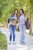 Hermanas adultas jovenes del gemelo de la raza mixta que comparten experiencia del teléfono celular Foto de archivo libre de regalías