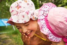 Hermanas alegres que juegan y que ríen con expresiones grandes en un parque Fotos de archivo
