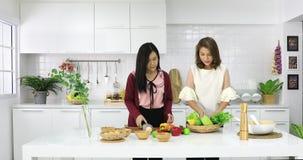 Hermanas asiáticas que preparan verduras y las frutas metrajes
