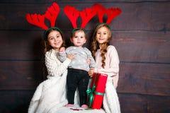 Hermanas bonitas divertidas sonrientes en cuernos de los ciervos en estudio Feliz Navidad y Feliz Año Nuevo Imagen de archivo libre de regalías