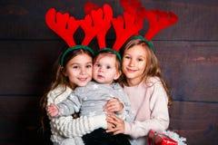 Hermanas bonitas divertidas sonrientes en cuernos de los ciervos en estudio Feliz Navidad y Feliz Año Nuevo Foto de archivo libre de regalías