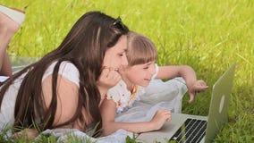 Hermanas bonitas jovenes felices que trabajan en el ordenador portátil en la mañana almacen de video