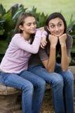 Hermanas cariñosas que se sientan junto en banco Foto de archivo libre de regalías
