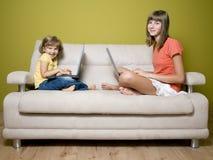 Hermanas con las computadoras portátiles en el sofá Imagen de archivo