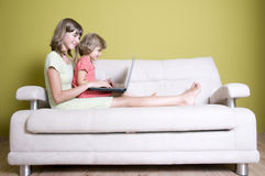 Hermanas con las computadoras portátiles en el sofá Foto de archivo