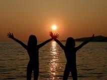 Hermanas con los brazos abiertos en puesta del sol Imagenes de archivo