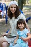 Hermanas con una PC de la tabla en el parque Imagen de archivo