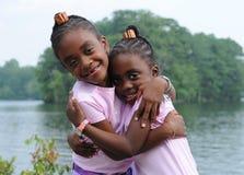 Hermanas de abrazo felices imágenes de archivo libres de regalías