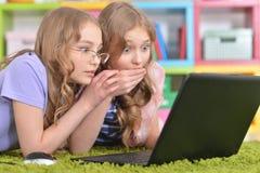 Hermanas de los adolescentes que usan el ordenador portátil Fotos de archivo libres de regalías