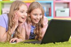 Hermanas de los adolescentes que usan el ordenador portátil Imagen de archivo libre de regalías