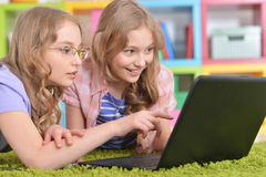 Hermanas de los adolescentes que usan el ordenador portátil Fotos de archivo