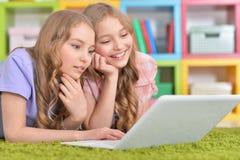 Hermanas de los adolescentes que usan el ordenador portátil Imágenes de archivo libres de regalías