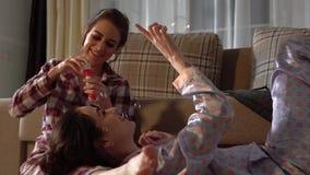 Hermanas de los gemelos que tienen burbujas que soplan de la diversión que llevan pajams bonitos Las muchachas se divierten Herma metrajes