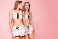 Hermanas de moda de los gemelos que presentan en fondo rosado Imagenes de archivo