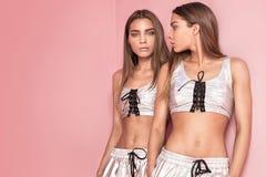 Hermanas de moda de los gemelos que presentan en fondo rosado Imagen de archivo