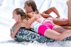 Hermanas de risa felices en un tobogán acuático Imagen de archivo