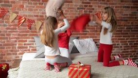 Hermanas de risa felices de los tríos en los pijamas que tienen una lucha de almohada en cama en casa El dormitorio es adornado p almacen de video