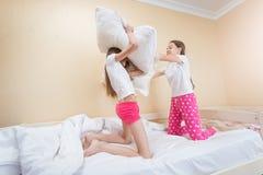 Hermanas del adolescente que tienen lucha de almohada en cama Fotos de archivo libres de regalías