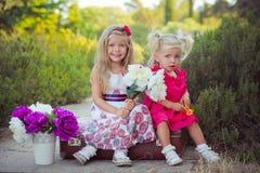 Hermanas dos ambos rubios con los ojos de azules claros profundos que llevan los vestidos coloridos que presentan en el prado del Foto de archivo