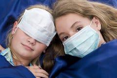 Hermanas en cama con la máscara protectora Imagen de archivo libre de regalías