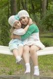 Hermanas en parque en un banco Imagenes de archivo