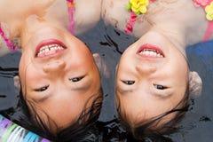 Hermanas en una piscina que vadea Foto de archivo