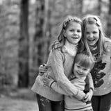 Hermanas felices amigos felices de los niños en bosque Fotos de archivo