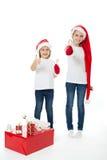 Hermanas felices en los sombreros de santa con los regalos de la Navidad imagen de archivo libre de regalías
