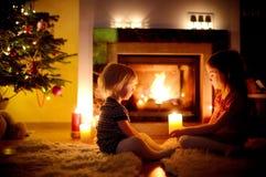 Hermanas felices por una chimenea en la Navidad Imagen de archivo libre de regalías
