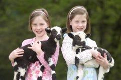 Hermanas gemelas con el cordero en Pascua fotos de archivo