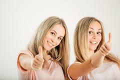 Hermanas gemelas con los pulgares para arriba en el fondo blanco Imagen de archivo