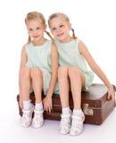 Hermanas gemelas con una maleta vieja grande. Imágenes de archivo libres de regalías
