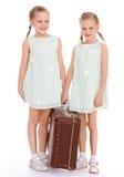 Hermanas gemelas con una maleta vieja grande. Imagen de archivo