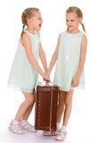 Hermanas gemelas con una maleta vieja grande. Imagenes de archivo