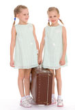Hermanas gemelas con una maleta vieja grande. Fotos de archivo libres de regalías