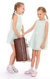 Hermanas gemelas con una maleta vieja grande. Fotografía de archivo