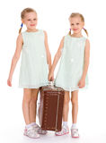 Hermanas gemelas con una maleta vieja grande. Fotografía de archivo libre de regalías