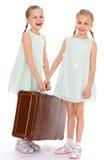 Hermanas gemelas con una maleta vieja grande. Foto de archivo libre de regalías