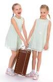 Hermanas gemelas con una maleta vieja grande. Fotos de archivo
