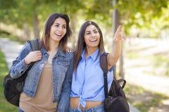Hermanas gemelas de la raza mixta que llevan las mochilas y que señalan afuera Foto de archivo