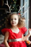 Hermanas gemelas de las niñas en los vestidos rojos que permanecen cerca de la ventana que espera Papá Noel Niños lindos con los  fotos de archivo