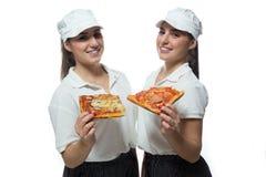 Hermanas gemelas hermosas con la pizza en el fondo blanco Imágenes de archivo libres de regalías