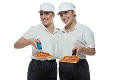 Hermanas gemelas hermosas con la pizza en el fondo blanco Foto de archivo