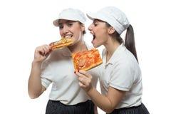 Hermanas hambrientas gemelas con la pizza en el fondo blanco Fotos de archivo libres de regalías