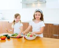 Hermanas hermosas del cocinero en la cocina que prepara la ensalada fotografía de archivo
